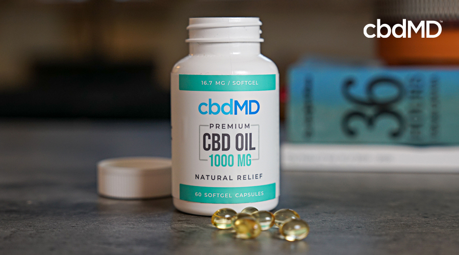 A bottle of 1000 mg cbd softgel capsules from cbdmd sits on a counter near some books