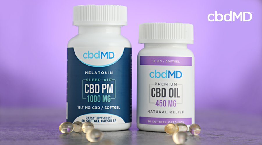 A bottle of 1000 mg cbd pm and 450 mg cbd softgel capsules sit next to one another