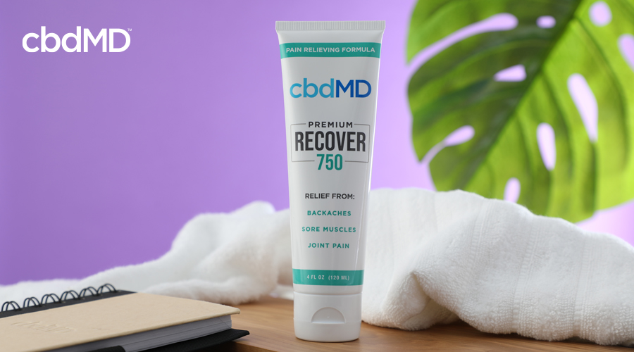A tube of 750 mg recover cream from cbdmd sits on a counter next to a white towel
