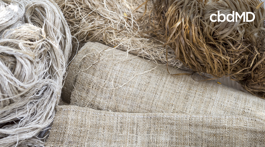 Cloth and rope made out of hemp lay in a pile among hemp fibers