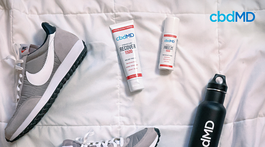 A bottle of cbd recover and cbd freeze from cbdmd sit on a comforter next to a sneaker and a water bottle