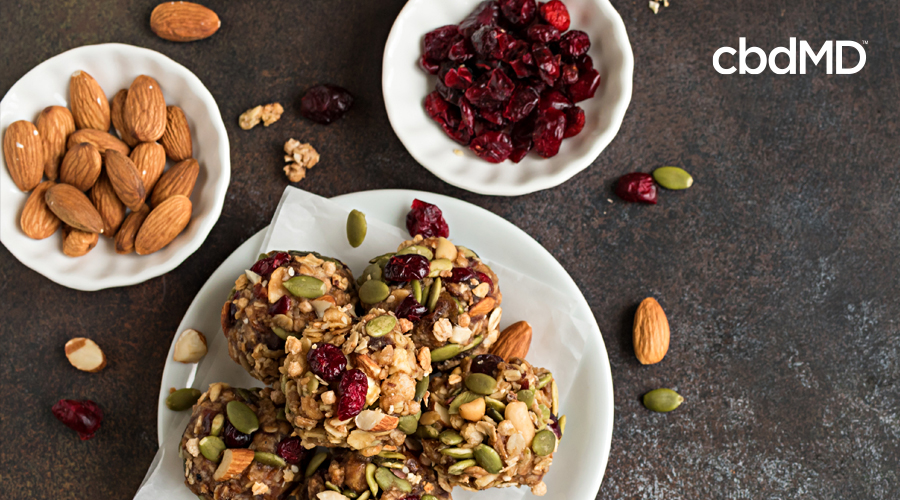 cbd berry healthy oatmeal bits sit on a plate surrounded by almonds and other fruit