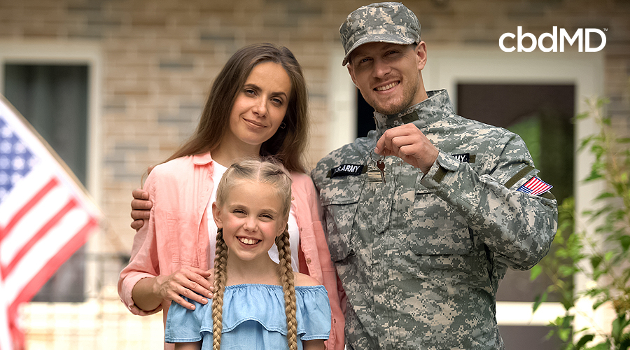 A military family stands together in front of their house with the american flag flying