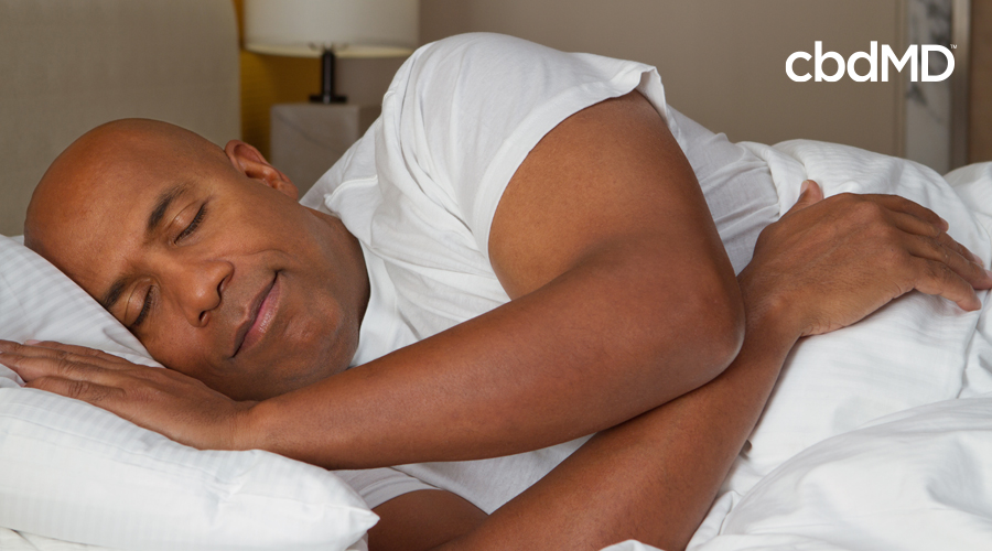 A man in a white tee shirt rests on his side fast asleep in bed