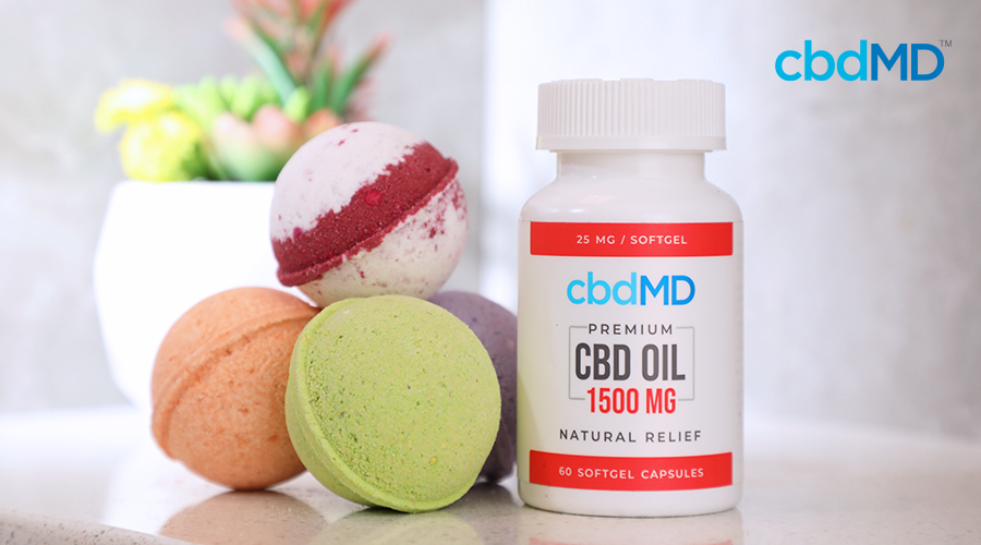A bottle of 1500 mg cbd oil capsules from cbdmd sits next to a small stack of cbd bath bombs