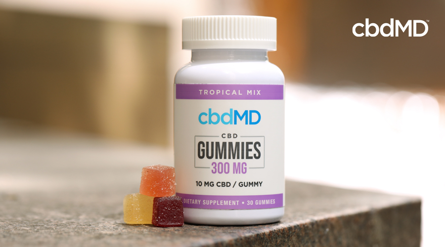 A bottle of 300 mg CBD gummies sits on a stone countertop