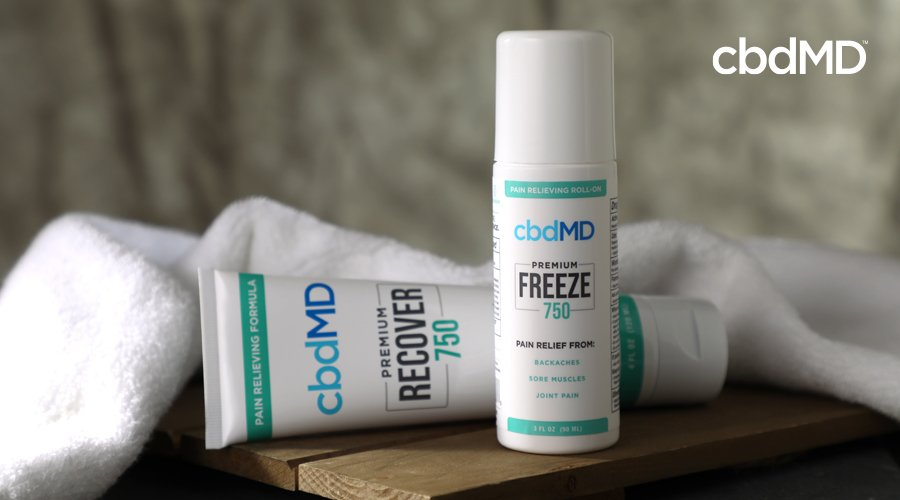 750 mg CBD Recover and 750 mg CBD Freeze sit on a wooden bench near a white towel