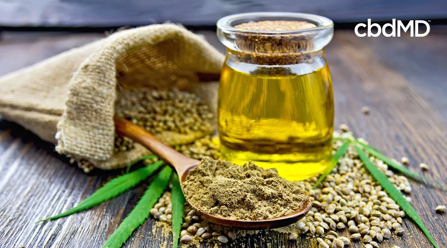 A glass bottle of cbd oil sits amongst natural ingredients
