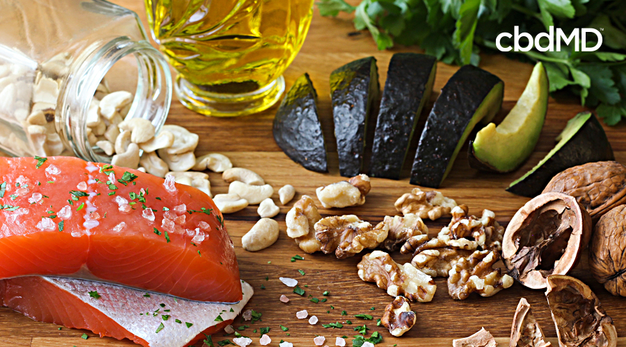 An assortment of healthy food that includes salmon, avocado, walnuts, and oils sits all together