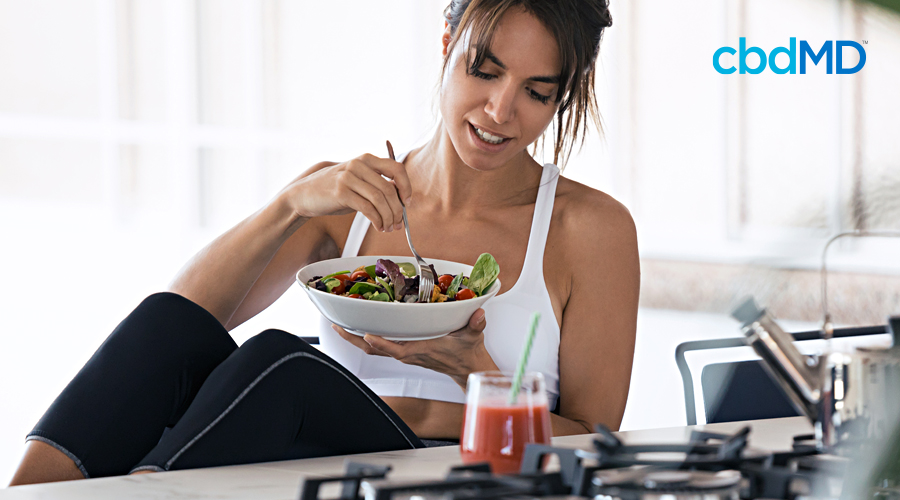 An attractive woman in workout clothes looks down at her bowl of healthy food