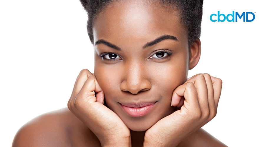 An attractive dark skinned woman shows off her impeccably clear skin