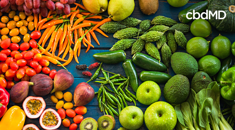 A large assortment of skin power foods sits together including multiple vegetables and fruits