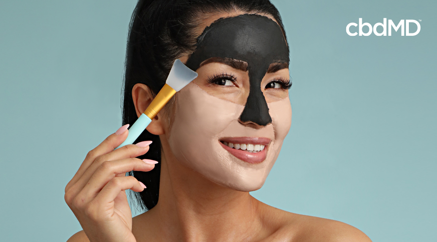 An attractive woman of asian descent paints a facemask on her face