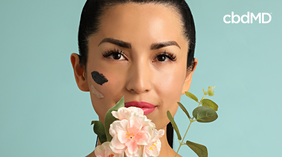 An attractive woman of asian descent looks from behind a flower with streaks of facemask on her face