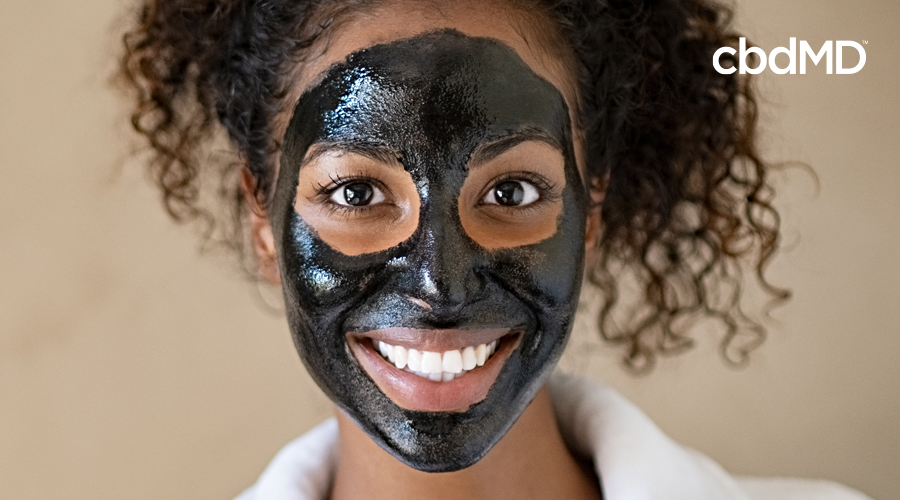 A dark skinned woman looks into the camera with charcoal me charcoal mask on her face