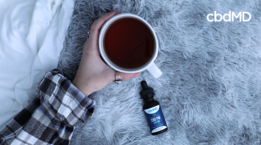 A bottle of cbd pm lays on a table next to an arm that is holding a cup of coffee