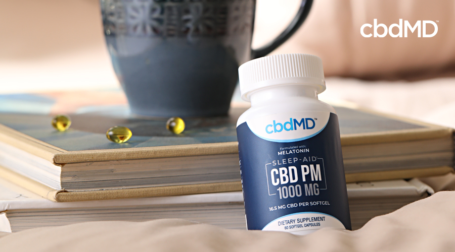 A bottle of cbd pm softgels sits on a bedside table next to a lamp