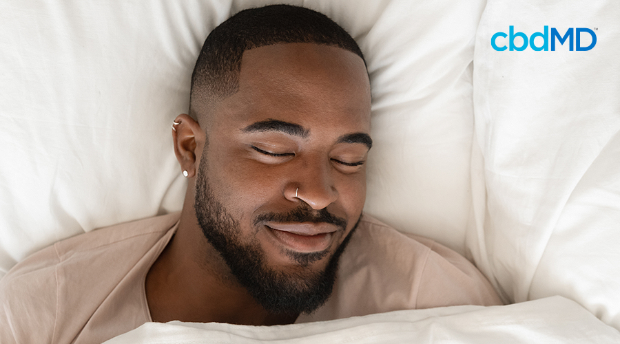 A dark skinned man sleeps comfortably with a large smile on his face