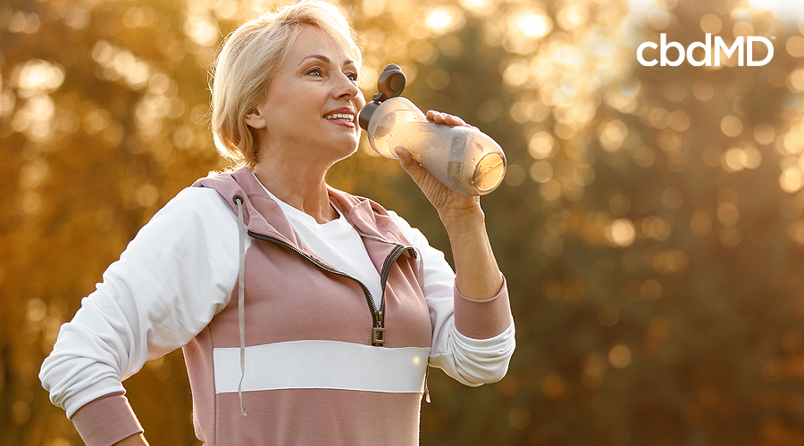 An older woman out for a morning walk takes a long drink from a travel cup