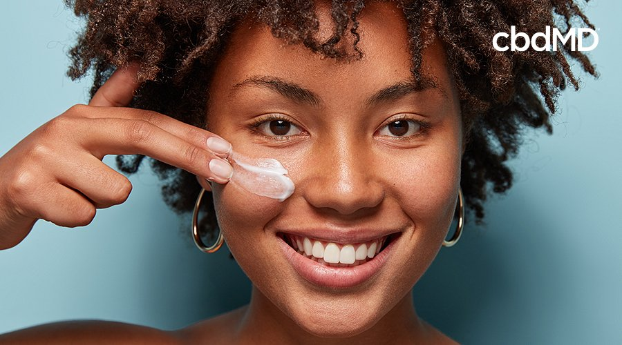 An attractive woman with dark skin and curly hair spreads cbd cream on her cheek