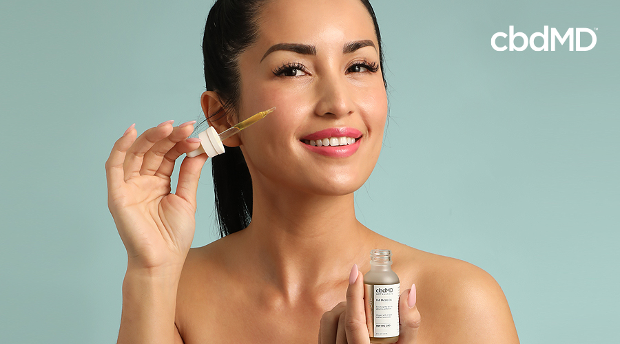 A beautiful woman of asian descent places cbdmd fountain of youth dynamic serum on her cheek