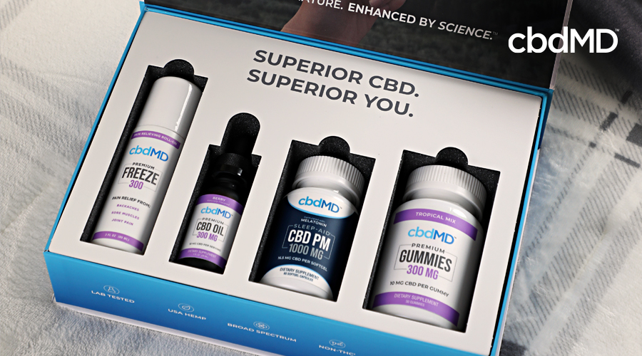 A cbd bundle with cbd freeze, cbd oil, cbd gummies, and cbd pm from cbdmd sits on a plaid blanket
