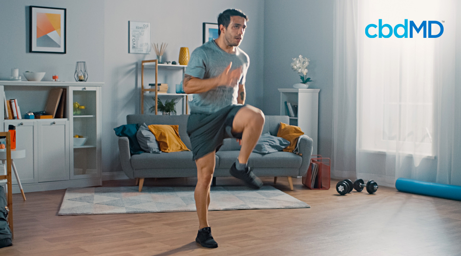 A dark haired man in exercise clothes runs in place in his living room