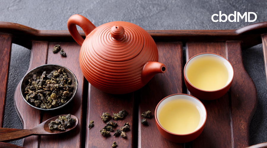 Dried tea leaves sit in a bowl next to a red teapot and two cups full of tea