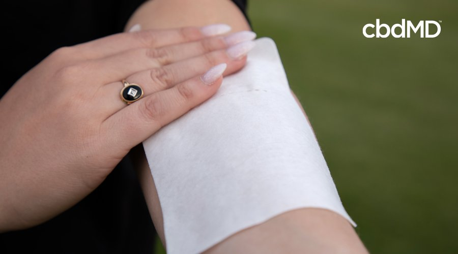Woman with manicured nails applies a CBD transdermal patch to left arm