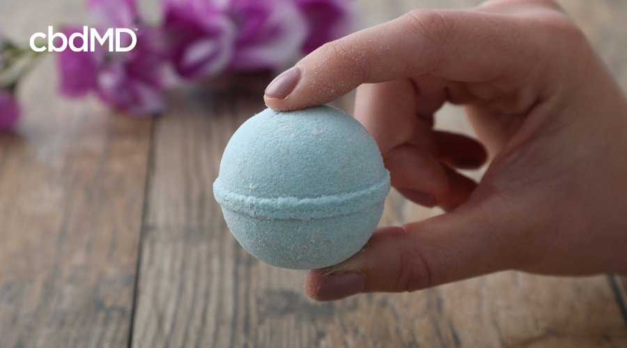 Hand holds blue Rejuvenate CBD bath bomb by cbdMD with pink flower in background