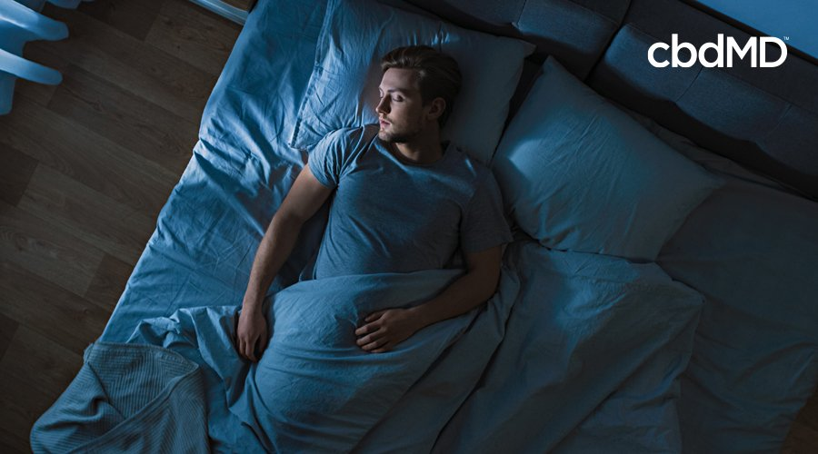 A man sleeps in a bed beneath fluffy covers