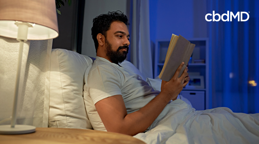 A bearded man sits in bed and reads by the light of a lamp