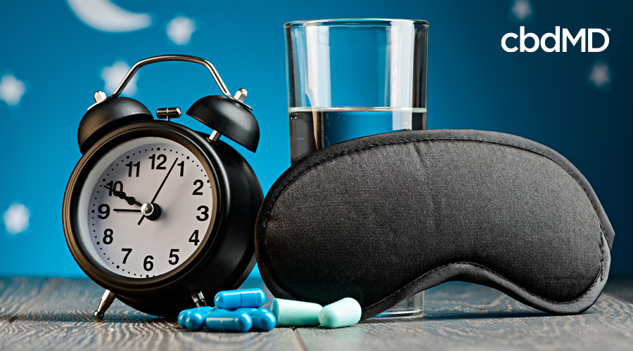 A traditional alarm clock sits alongside cbd pm, a sleep mask, and a glass of water