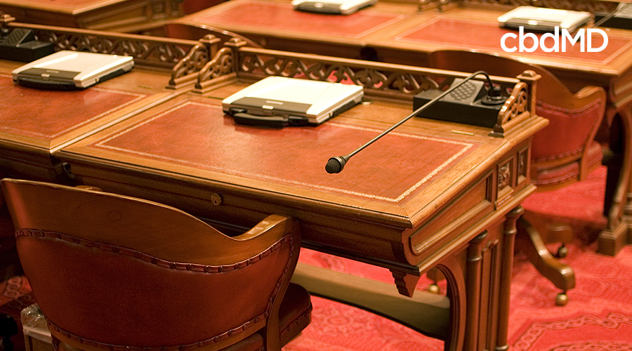 A seat in a legislative chamber sits empty with a microphone pointing back and a laptop sitting on the desk