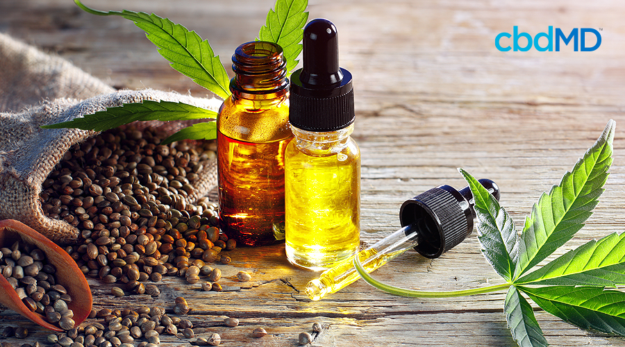 Two bottles of cbd oil, one of them open, sit next to a full dropper beside hemp seeds and a hemp leaf