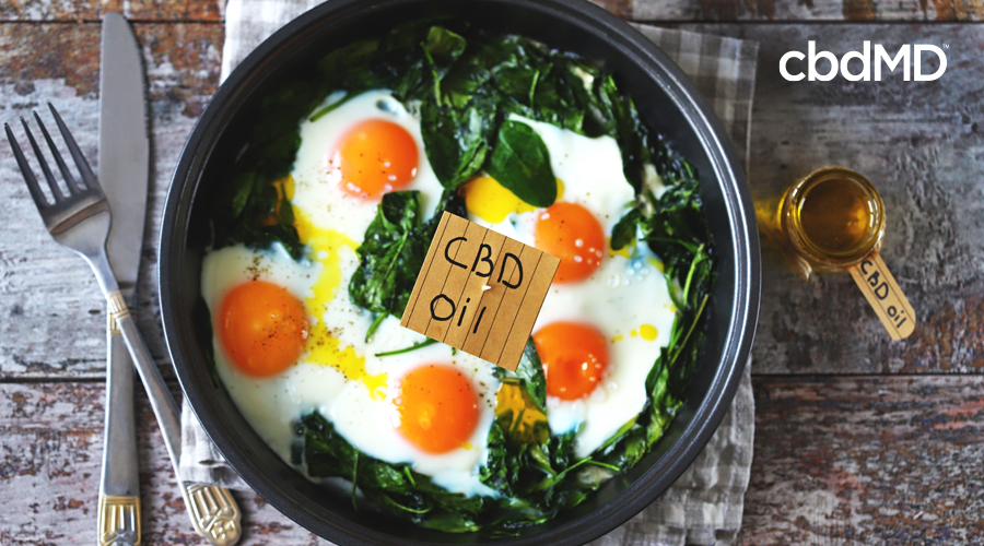 A bowl of fried eggs sits next to a knife and fork with a little sign that says cbd oil