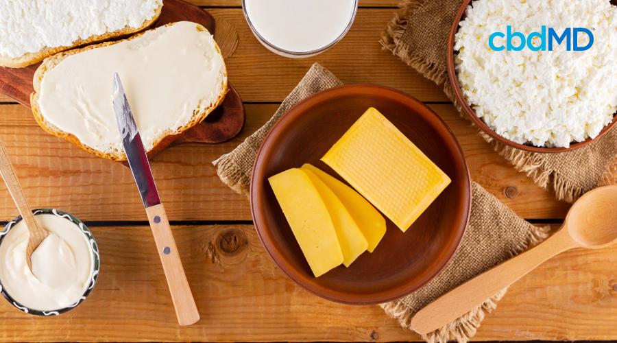 A bowl of sliced cheddar cheese sits on a wooden table next to buttered bread