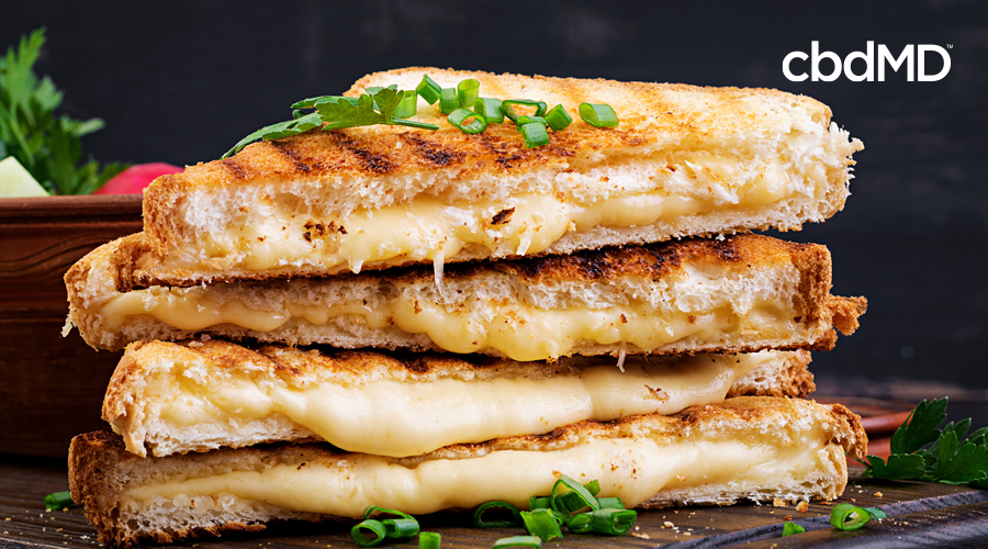A stack of pressed grilled cheese sandwiches sits on a wooden table