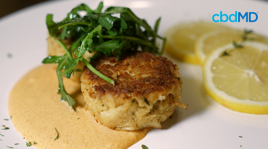 crab cakes with cream sauce sit on a white plate near lemon slices