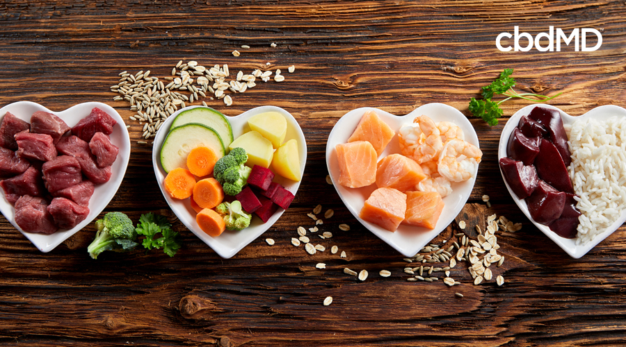 An assortment of healthy food choices for pets sits in heart shaped bowls