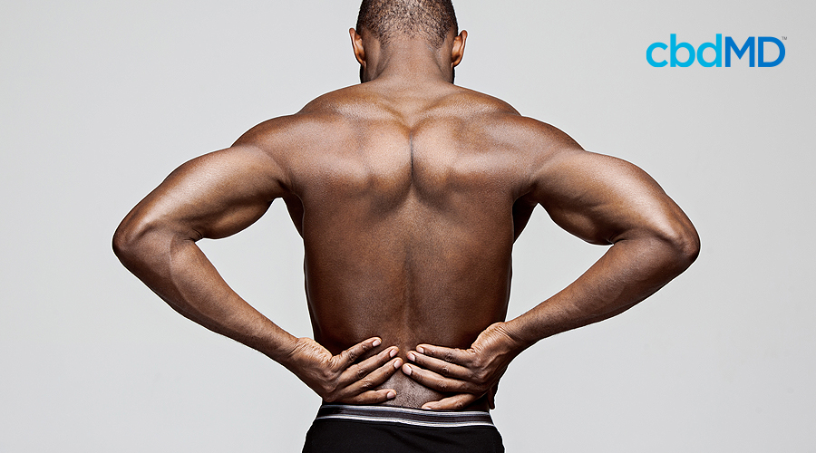 A muscular man with dark skin holds the sides of his back in apparent pain