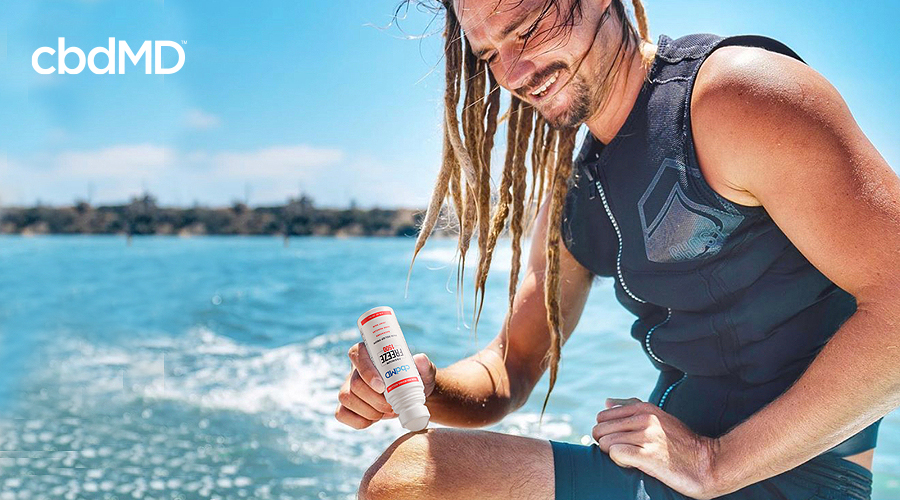 A man with dreadlocks on a surf board rubs cbd freeze topical onto his knee