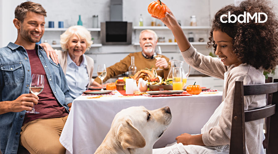 A family sits around a dinner table with their dog looking on