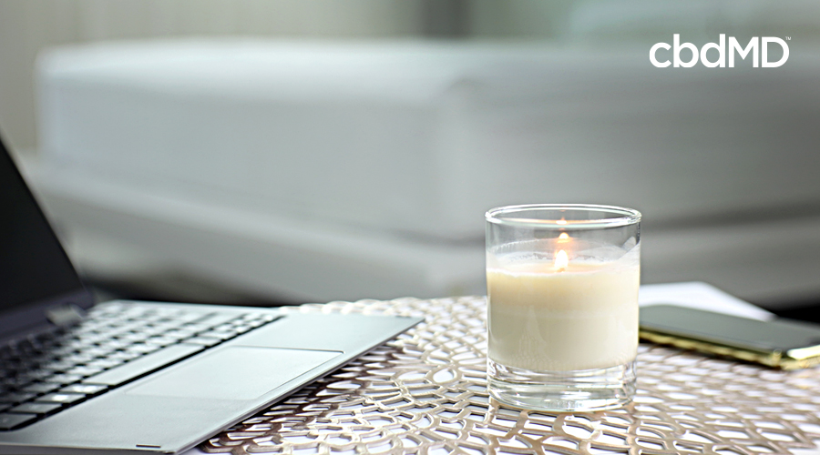 A lit candle sits on a desk next to an open computer