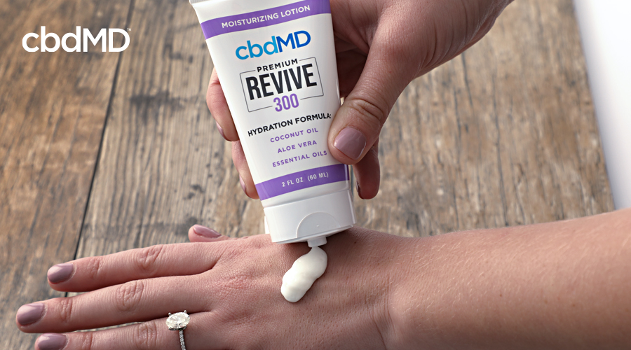 A woman squeezes cbd revive from cbdmd onto her hand