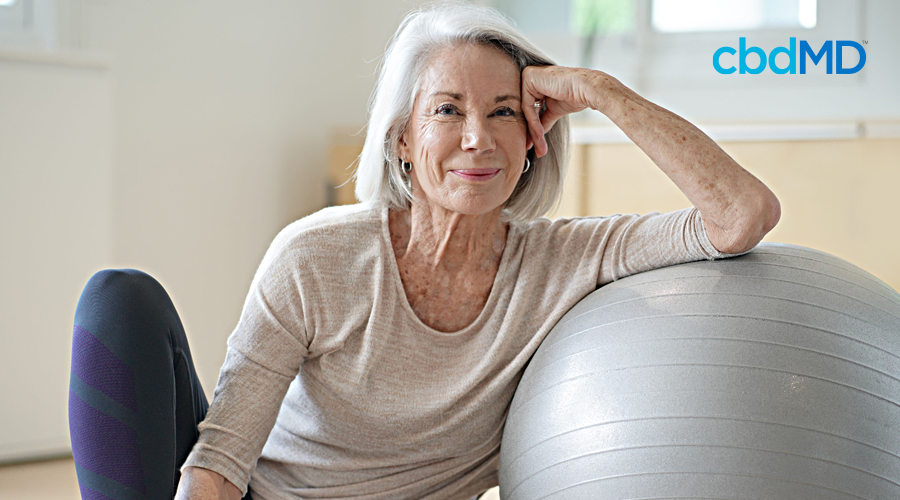 An older woman in workout clothes sits against an exercise ball