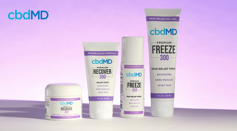 Topical products from cbdmd including cbd freeze and cbd recover sit on a white table against a purple background