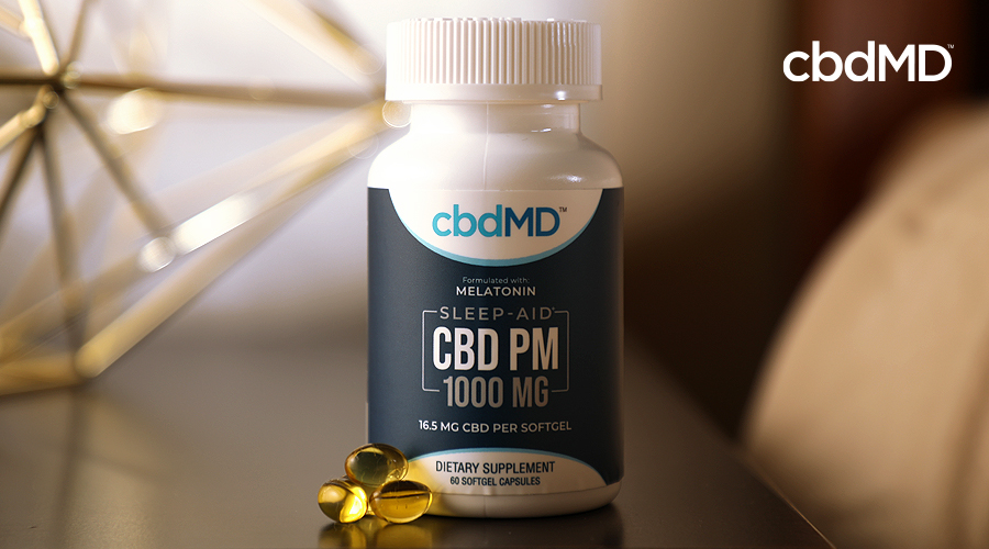 A bottle of 1000 mg cbd pm capsules from cbdmd sits on a nightstand next to a bed