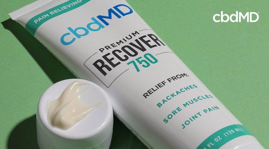 A tube of 750 mg cbd recover from cbdmd lays on its side against a green background