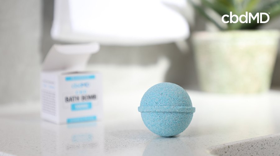 A blue cbd bath bomb from cbdmd sits on a bathroom counter with the box just visible in the background